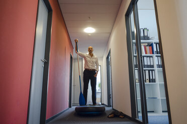 Businessman standing on paddle board, exercising in office corridor - KNSF04488