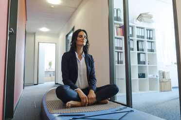Businesswoman practicing yoga on paddle board, daydreaming in office - KNSF04500
