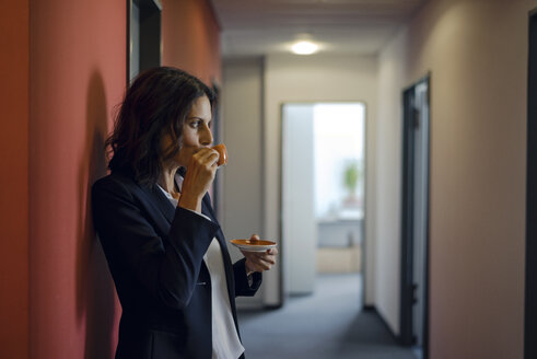 Mature businesswoman standing in office corridor, drinking coffee - KNSF04503