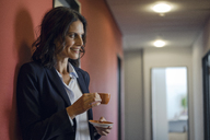 Mature businesswoman standing in office corridor, drinking coffee - KNSF04506
