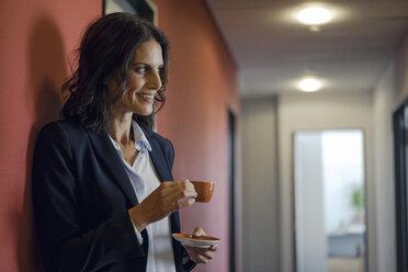 Mature businesswoman standing in office corridor, drinking coffee - KNSF04506
