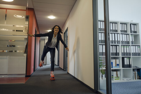 Mature businesswoman rollerskating in office corridor - KNSF04509