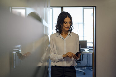 Businesswoman in office reading messages on her smartphone - KNSF04512