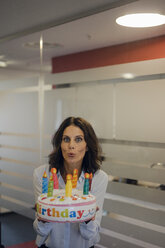 Businesswoman holding birthday cake, blowing out candles - KNSF04521