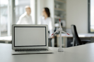 Laptop and model of wind wheel on shelf in office, with two people talking in background - KNSF04524