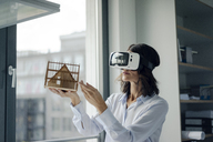Woman holding architectural model of house, using VR glasses - KNSF04527