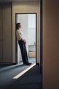 Businesswoman leaning relaxed in door frame of her office - KNSF04536
