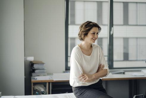 Successful businesswoman sitting on desk in her office - KNSF04539