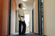Businesswoman standing in office corridor, holding laptop - KNSF04545