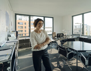 Successful businesswoman standing in her office with arms crossed - KNSF04551