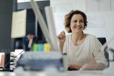 Businesswoman working in office, sitting at desk - KNSF04557