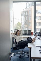 Businesswoman relaxing in office with feet on desk - KNSF04560