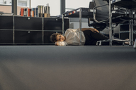 Tired businesswoman sleeping on floor under her desk - KNSF04563