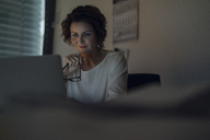 Businesswoman working overtime, using laptop, holding glasses - KNSF04572