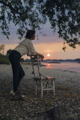 Woman leaning on a chair at the river, watching sunset - KNSF04581