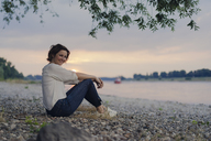 Woman sitting at the river, watching sunset - KNSF04584