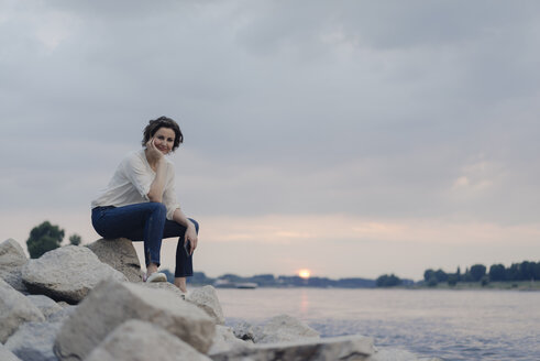 Woman sitting at the river, watching sunset - KNSF04587