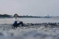 Woman sitting at the river at dusk - KNSF04593