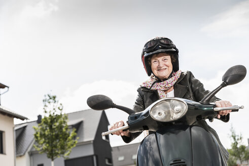 Active senior lady riding motor scooter in the city - UUF14915