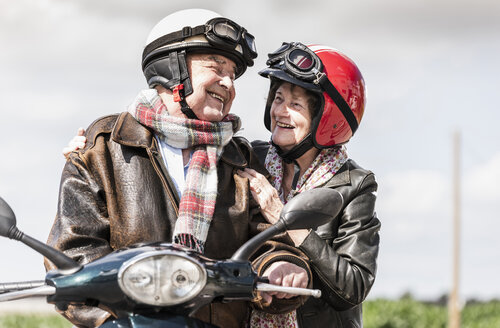 Happy senior couple riding motor scooter - UUF14924