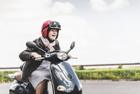 Active senior lady riding motor scooter on the road - UUF14930