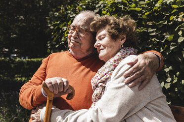 Senior couple sitting on bench in a park, with arms around - UUF14933