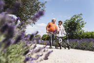 Senior couple walking in park, woman using wheeled walker - UUF14948