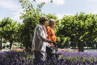 Senior couple walking in park, woman using wheeled walker - UUF14951