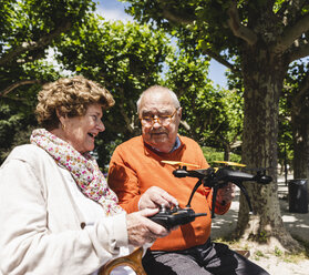 Senior couple playing with a drone in park - UUF14957
