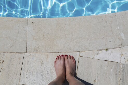 Woman's feet at poolside - JUNF01130