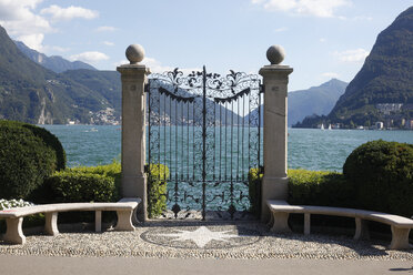 Switzerland, Lugano, view to Lake Lugano behind wrought-iron gate - JT01049
