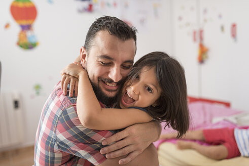 Happy father hugging daughter at home - JASF01914