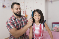 Smiling father combing daughter at home - JASF01917