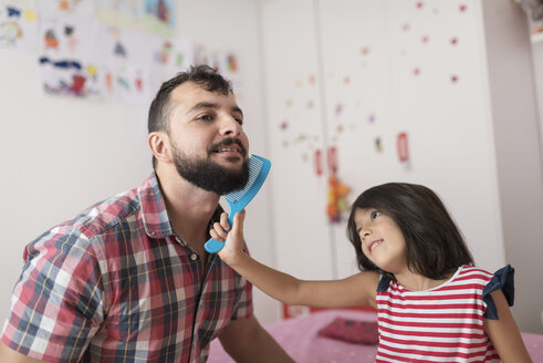 Little girl combing her father's beard - JASF01923