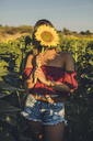 Young woman standing in a field holding a sunflower in front of her face - ACPF00296