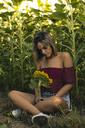 Young woman sitting in a field of sunflowers with a sunflower in her hand - ACPF00299
