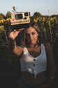 Young woman in a field of sunflowers holding an instant camera - ACPF00305