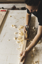 Carpenter using plane on piece of wood in workshop - PSIF00042