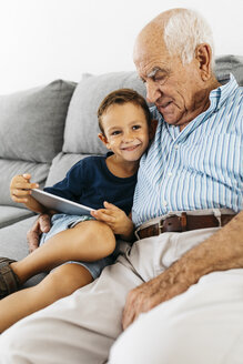 Portrait of happy little boy with digital tablet sitting besides his grandfather on the couch at home - JRFF01807