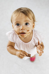 Portrait of little girl eating chocolate cookie - JRFF01813
