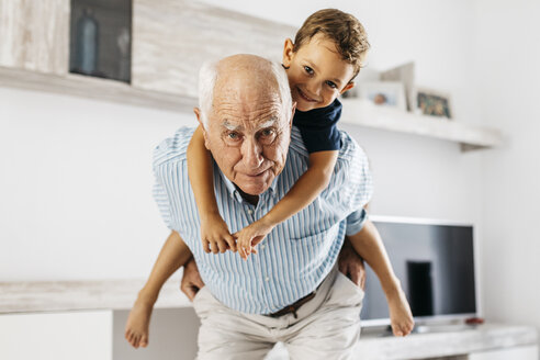 Portrait of grandfather giving his grandson a piggyback ride in the living room - JRFF01816