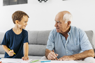 Grandfather and grandson drawing together with coloured pencils at home - JRFF01819