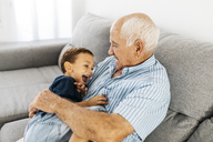 Grandson and grandfather laughing while tickling each other on the couch - JRFF01825