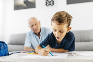 Portrait of little boy drawing with coloured pencils while his grandfather in the background watching him - JRFF01828