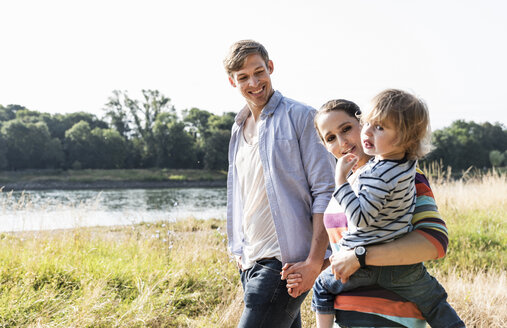 Happy family walking at the riverside on a beautiful summer day - UUF14961