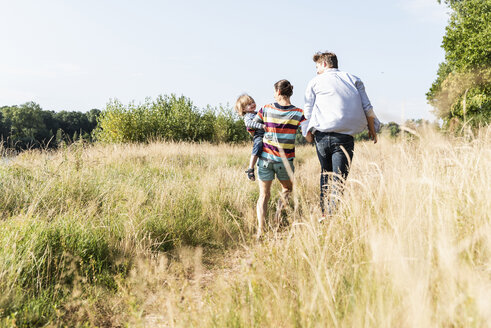 Happy family walking at the riverside on a beautiful summer day - UUF14964