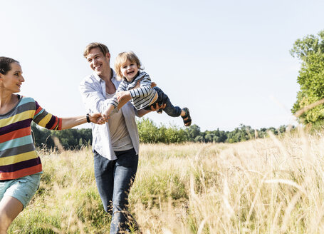 Happy family walking at the riverside on a beautiful summer day - UUF14970