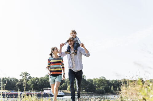 Happy family walking at the riverside on a beautiful summer day - UUF14994