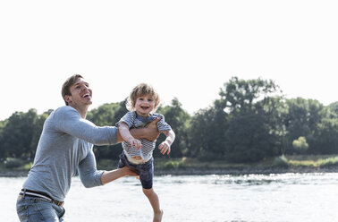 Father and son having fun at the riverside - UUF15006