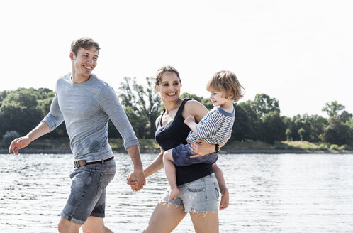 Happy family walking at the riverside on a beautiful summer day - UUF15012